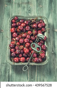Vintage tray of cherries and old stone remover.Toned