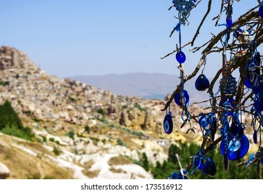 A vintage tree decorated with non-commercial Evil Eyes & pots at Goreme National Park, Cappadocia. Evil Eye is a Turkish traditional ornament dating back to Paganism.