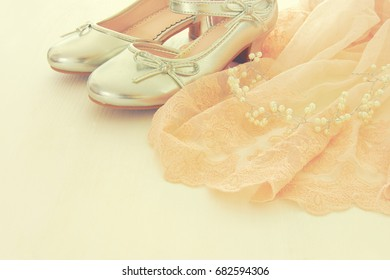 Vintage tulle pink chiffon dress and silver shoes on wooden white floor. Wedding, bridesmaid and girl's party concept