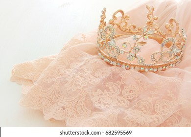 Vintage tulle pink chiffon dress and diamond tiara on wooden white table. Wedding and girl's party concept.