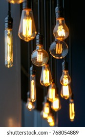 Vintage tungsten filament multiple lamps of different size and style hanging from the ceiling on a black wires as an interior design concept. Energy and design concept