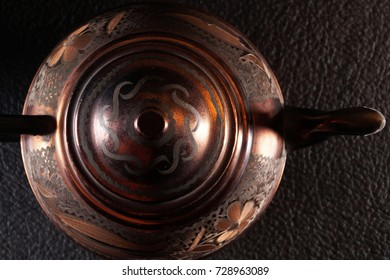The vintage Turkish teapot on black background. Copper teapot.
