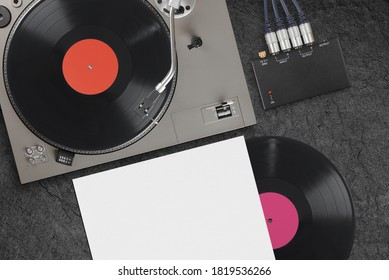 Vintage turntable with vinyl LP record on a concrete background. Top view.