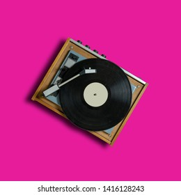 vintage turntable vinyl record player on pink background. retro sound technology to play music