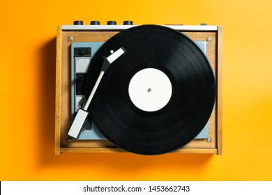 vintage turntable vinyl record player on orange background. retro sound technology to play music