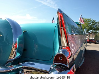 Vintage turquoise and silver car with close up of tail fins and rear lights American flag on front of car.
