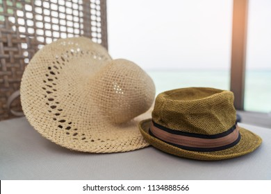 Vintage two fashion hats on sofa, with sea background, vacation holiday concepts.