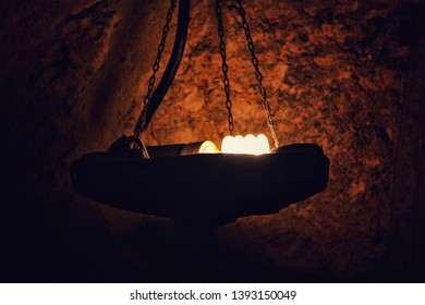 Vintage type pic of a lamp inside a cave lighted in the dark.Thus it predicts the innovation in the stages of light from fires to bulbs.