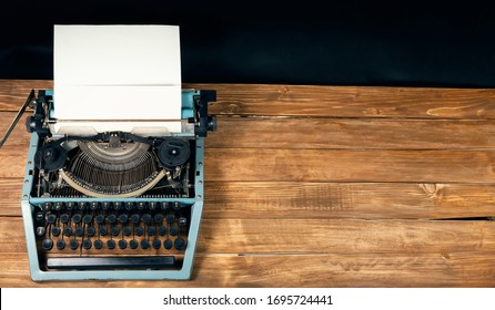 Vintage typewriter with blank paper stands on a wooden table
