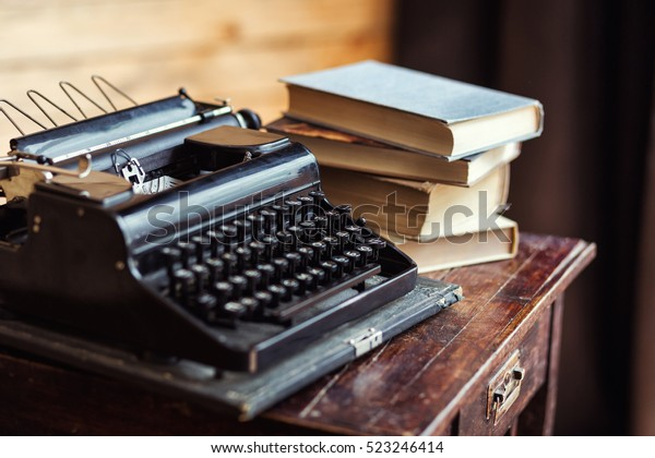 vintage typewriter and books on the table with blank paper on wooden desk