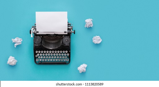Vintage typewriter and crumpled papers over blue background with copy space