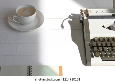 Vintage typewriter and a cup of coffee on white table at top view.
