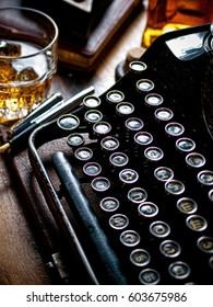 Vintage typewriter, glass of whiskey on the rocks on a writer's table