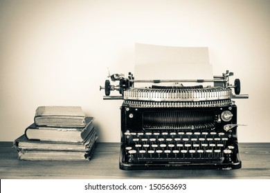 Vintage typewriter, old books on table sepia photo