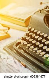Vintage typewriter, old books on table