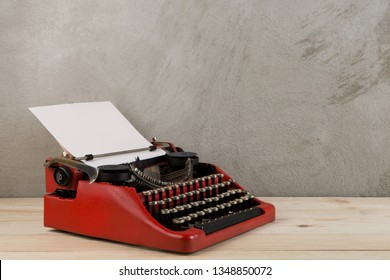 vintage typewriter on the table with blank paper on wooden desk - concept for writing, journalism, blogging