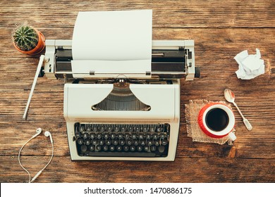 Vintage typewriter on a wooden table with cup of coffee and some stuff. Writing or blogging concept.