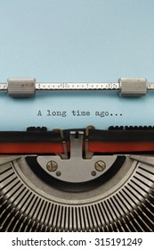 """Vintage Typewriter With Phrase """"A long time ago"""" Typed on Blue Paper Vertical Photograph"""