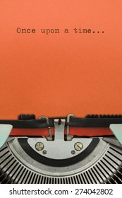 """Vintage Typewriter With Phrase """"Once upon a time..."""" Typed in Orange Paper"""