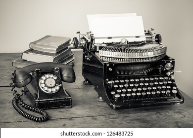 Vintage typewriter, telephone, old books on table desaturated photo