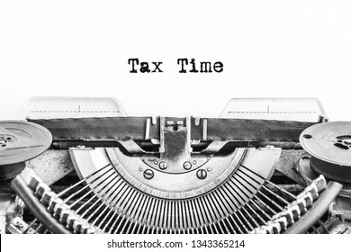 Vintage typewriter with typed word tax time. pay taxes