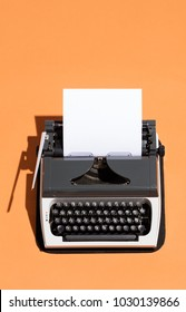 Vintage typewriter with a white blank sheet of paper in it. Journalism. Top view.