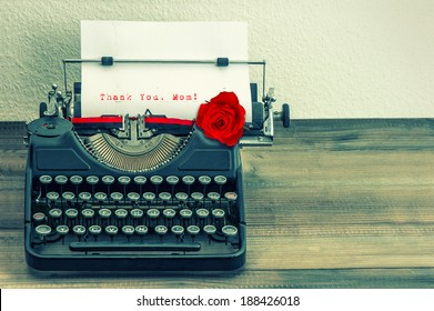 vintage typewriter with white page and red rose flower. sample text Thank You, Mom! Mother's Day concept. retro style toned picture
