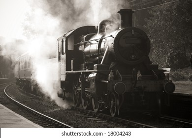 vintage unmarked steam train entering old fashioned station