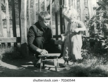 Vintage unretouched photo of brother and sister playing outdoor