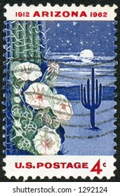 A vintage US Postage Stamp depicting the 50th anniversary of Arizona statehood with a night time desert scene with cactus and moon
