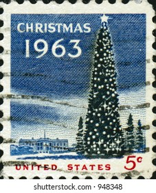 A vintage US potage stamp from 1963 with a christmas tree and white house in the background.