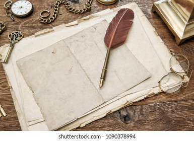 Vintage used paper with feather pen. Antique office supplies and accessories on wooden table