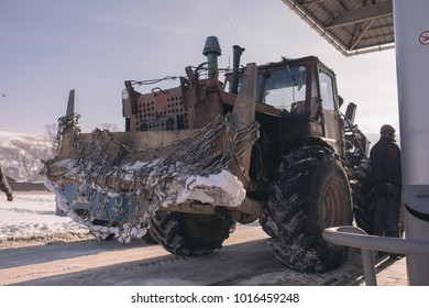 Vintage ussr tractor on petrolium station with chain winter time