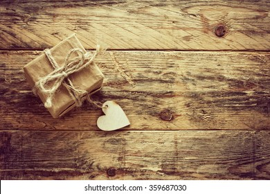 vintage valentine's day small gift box on old wooden table, retro sepia toned