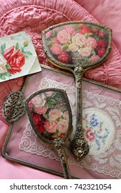 Vintage Victorian brush, mirror and comb vanity dressing table set with ornate handles and roses design on an antique brass, lace and glass tray and pink satin fabric.