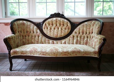 A vintage victorian high cameo back floral sofa with dark carved  woodwork sits in a sunroom of an old home.