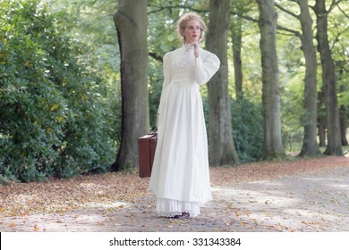 Vintage victorian woman holding suitcase standing in avenue.