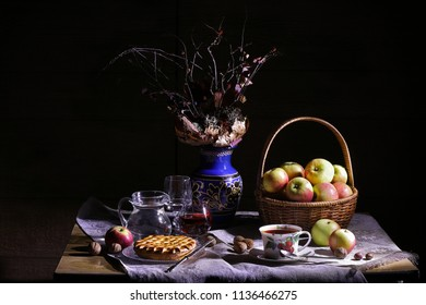 Vintage village still life : autumn leaves in a clay vase, basket of apples, pie, silver knife, antique tea cup, jar, glass of wine, hazelnuts, walnuts and chestnut on a table in light and shadows.