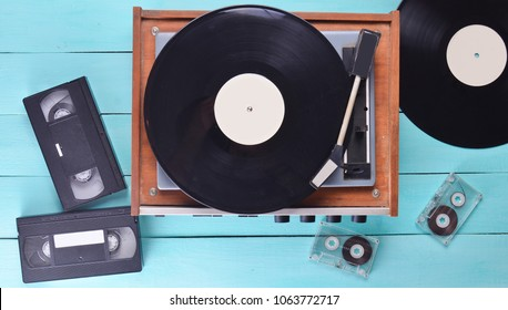 Vintage vinyl player with plates, video cassette, audio cassette on a blue wooden background. Top view. Retro media technologies