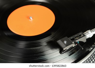 Vintage vinyl record with empty orange label played on the turntable with audiophile cartridge.