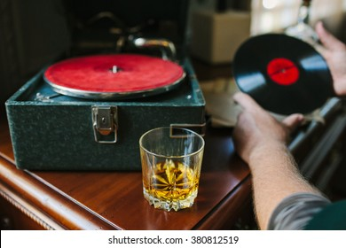 Vintage vinyl record with red label, vintage gramophone and glass of whiskey