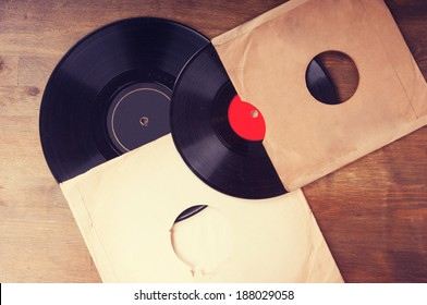 Vintage vinyl records in an envelope on a wooden table
