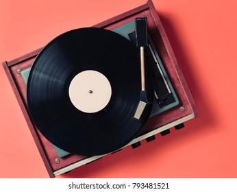 Vintage vinyl turntable with vinyl plate on an orange background. Entertainment 70s. Listen to music. Top view.