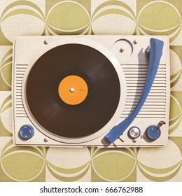 Vintage vinyl turntable player on top of retro green wallpaper