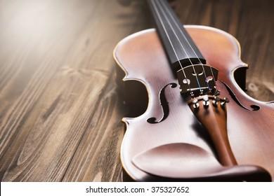Vintage violin on the brown wooden background.