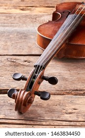 Vintage violin on wooden planks. Viola musical instrument on old wooden boards, vertical image. Cello close up of scroll and peg box. Classical instrument of baroque style.