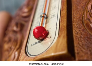 Vintage violin thermometer with red mercury and wooden background