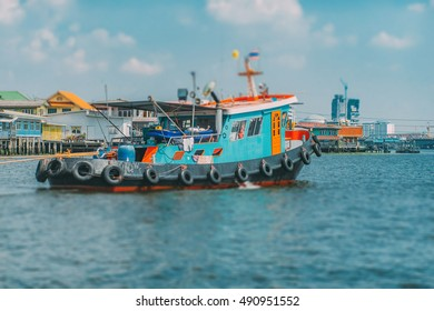 Vintage vivid tugboat tow ship on the river bay at the Chao Phraya river in Bangkok, Thailand. Industrial background. Travel inspiration. Vintage effect.