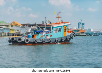 Vintage vivid tugboat tow ship on the river bay at the Chao Phraya river in Bangkok, Thailand. Industrial background. Travel inspiration. Vintage effect. Tilt-shift effect.