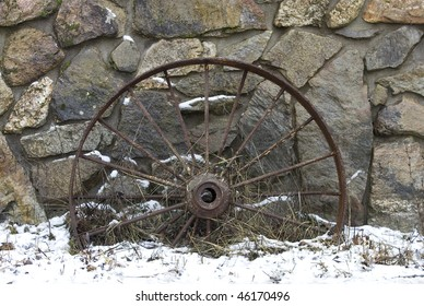A vintage wagon wheel leans against this rock wall.